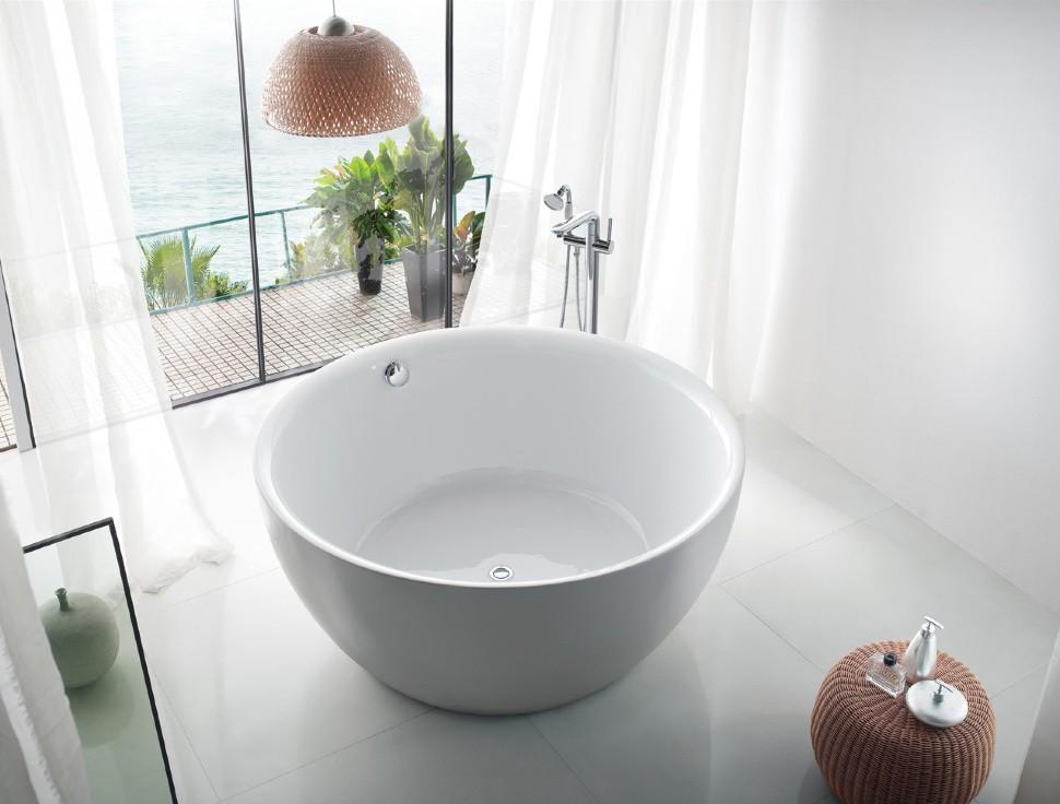 Круглая ванна из чугуна перед панорамным окном
