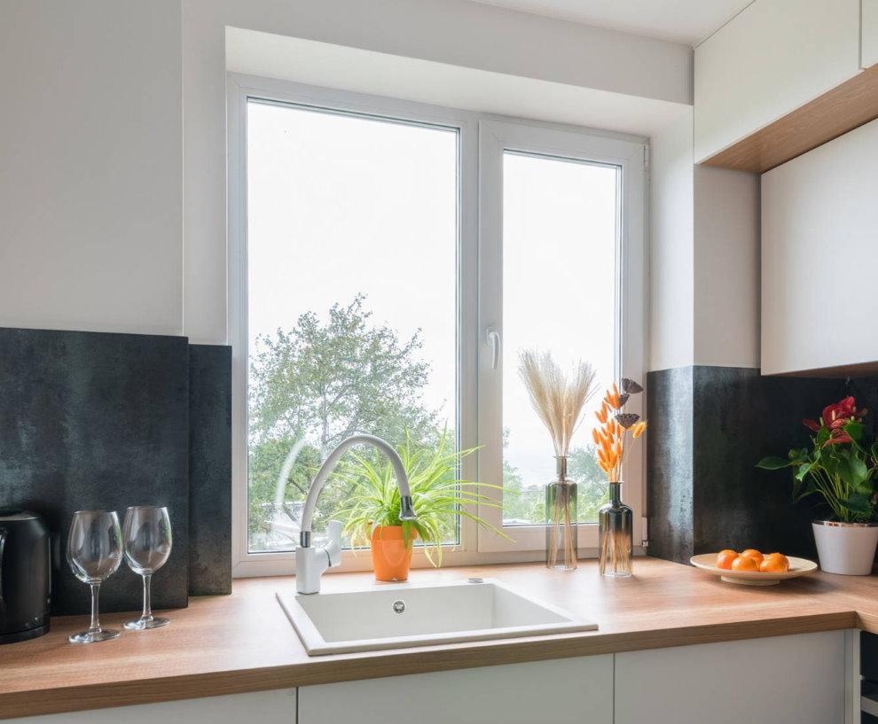 Мойка перед кухонным окном в квартире