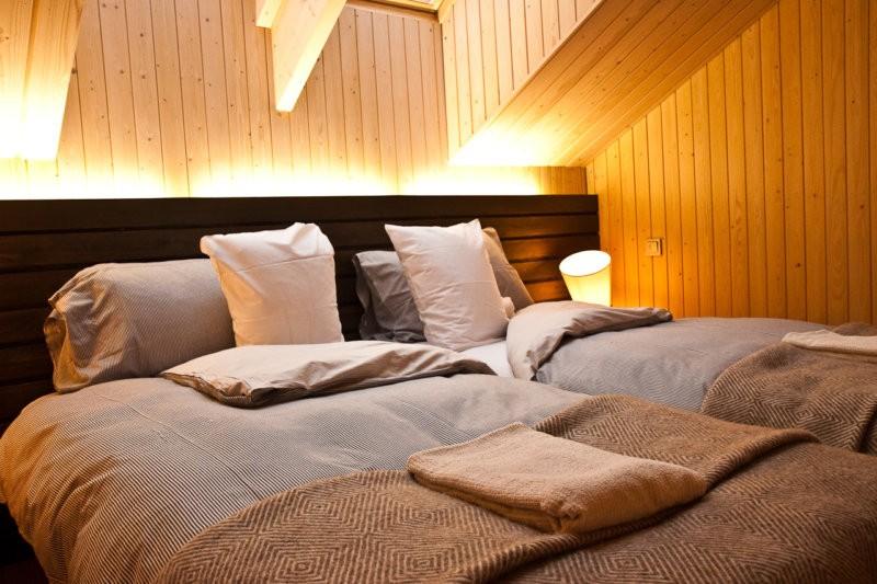 Подсветка изголовья кровати в спальне с деревянной отделкой