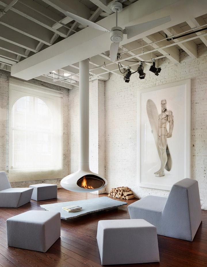 Белый островной камин в светлой гостиной