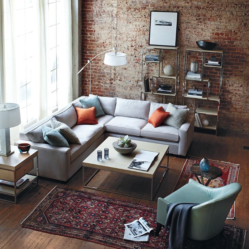 Угловой диван в гостиной с кирпичной стеной