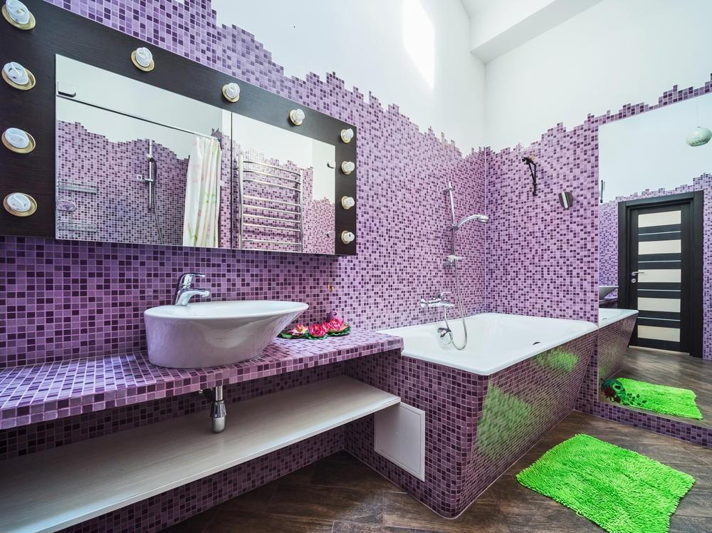 Зеленый коврик на полу ванной с мозаикой