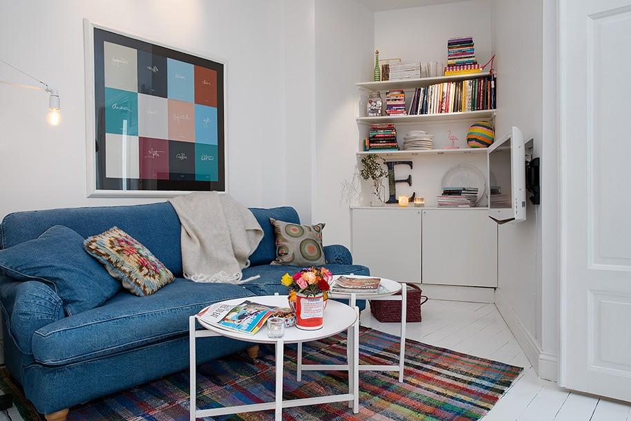 Синий диван в небольшой гостиной скандинавского стиля