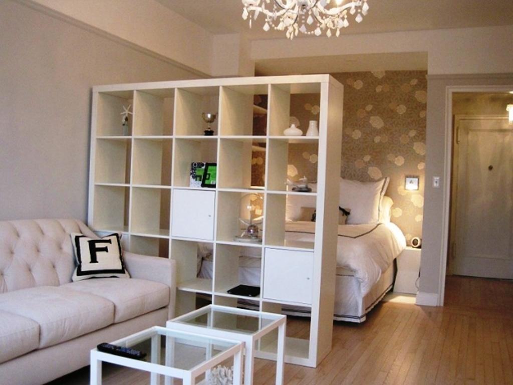 Белый стеллаж в гостиной с кроватью