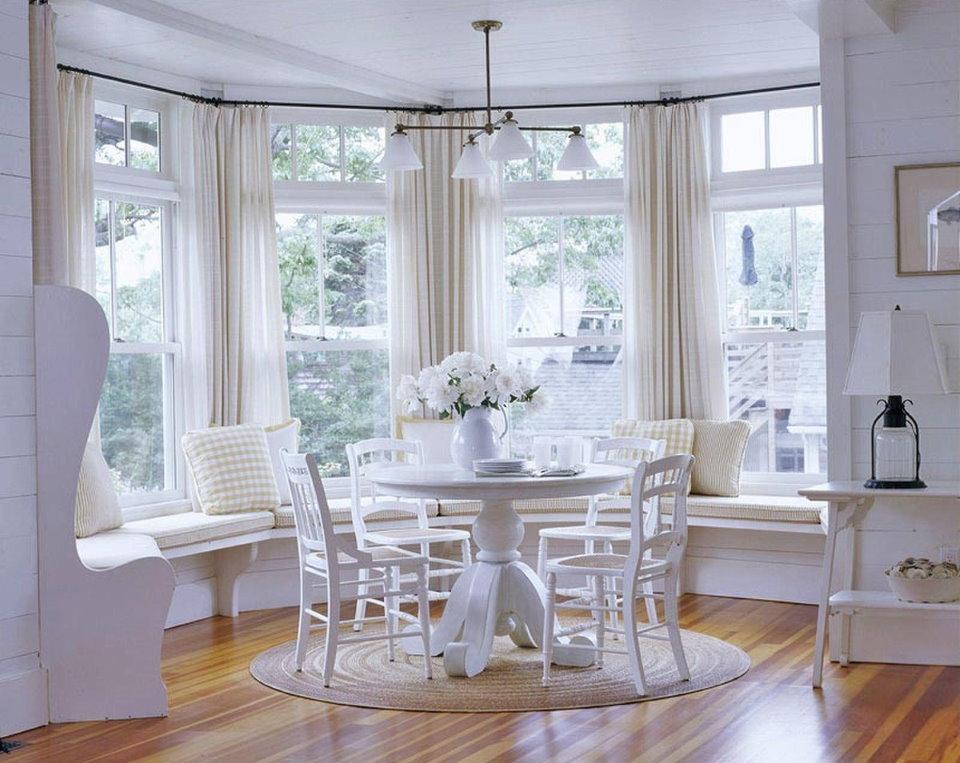 Круглый стол белого цвета в эркере гостиной