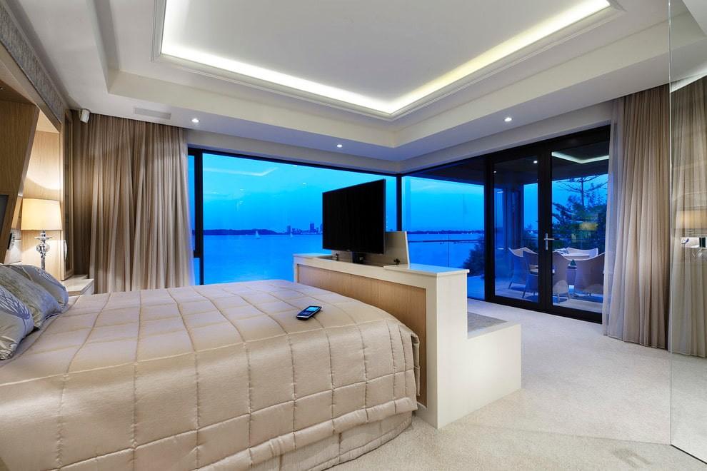 Выдвижной телевизор в спальне с панорамными окнами
