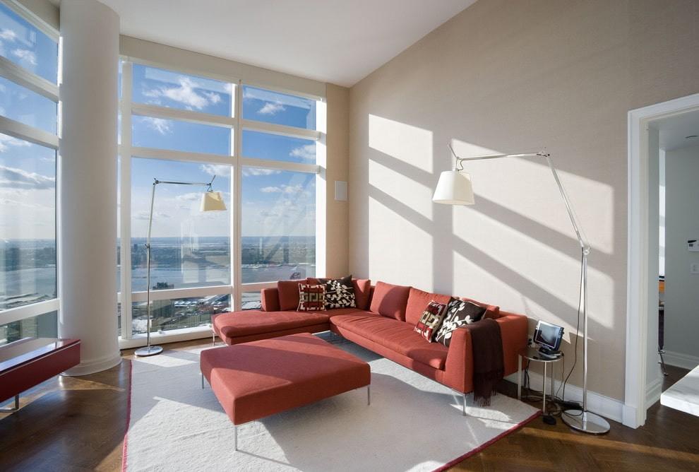 Угловой диван с оттоманкой в гостиной с большими окнами