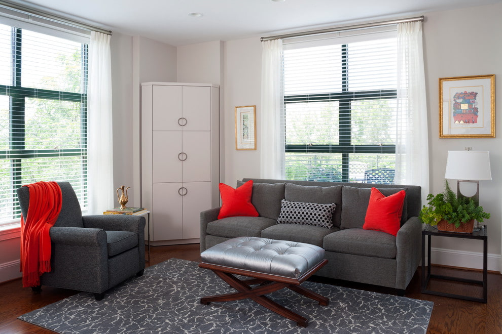 Белый шкаф в углу гостиной с серым диваном