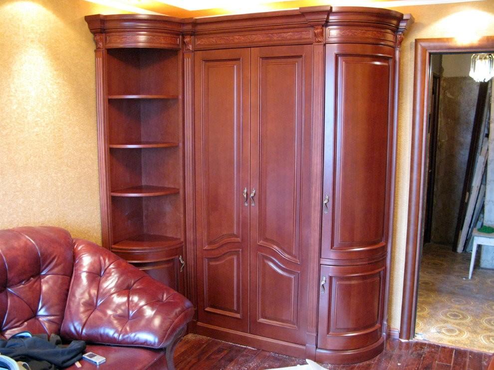 Классический угловой шкаф в комнате с кожаным диваном