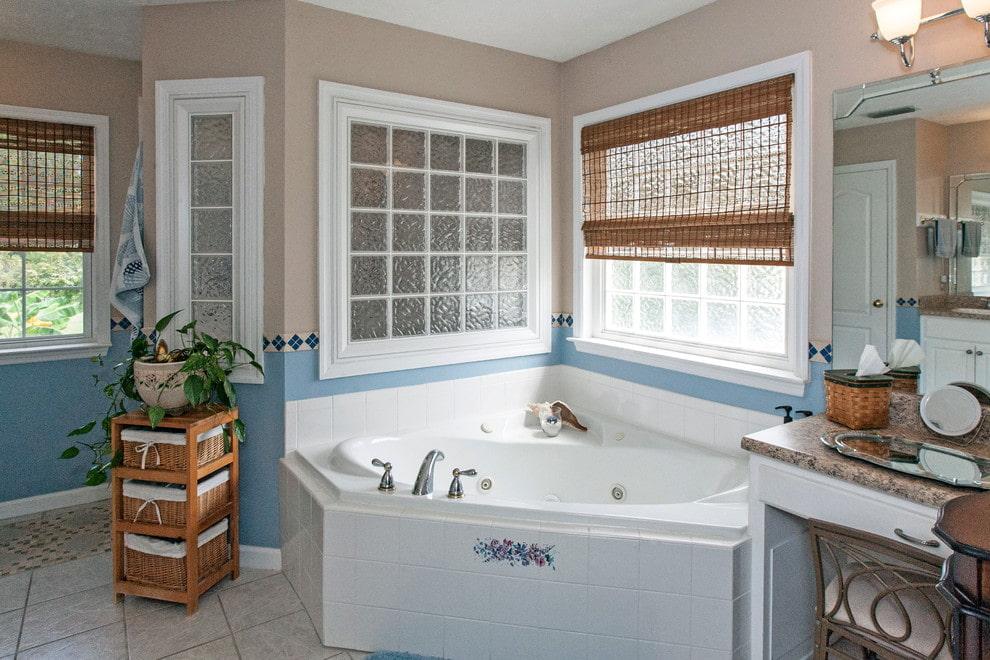 Угловая ванна из чугуна перед окном с бамбуковой шторой