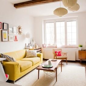 Желтый диван в комнате с деревянными балками