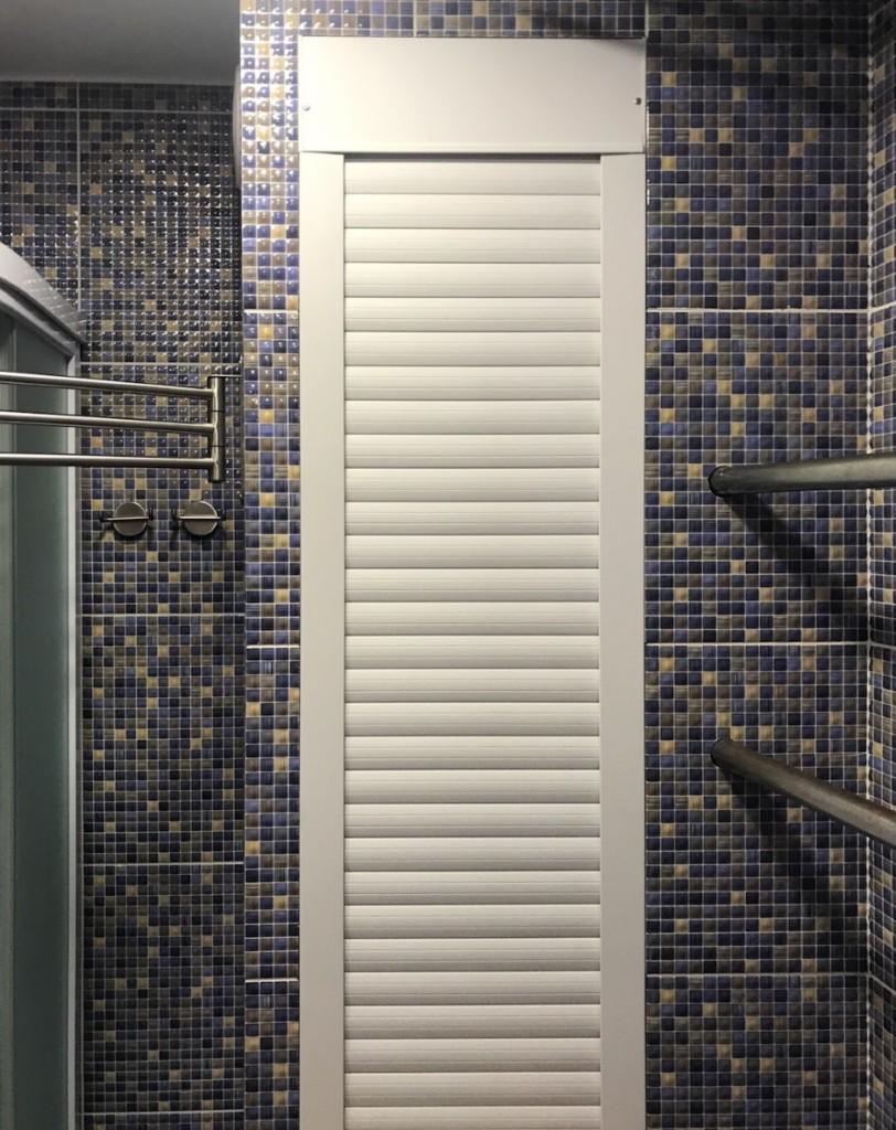 Белые пластиковые жалюзи на фоне стены с керамической мозаикой