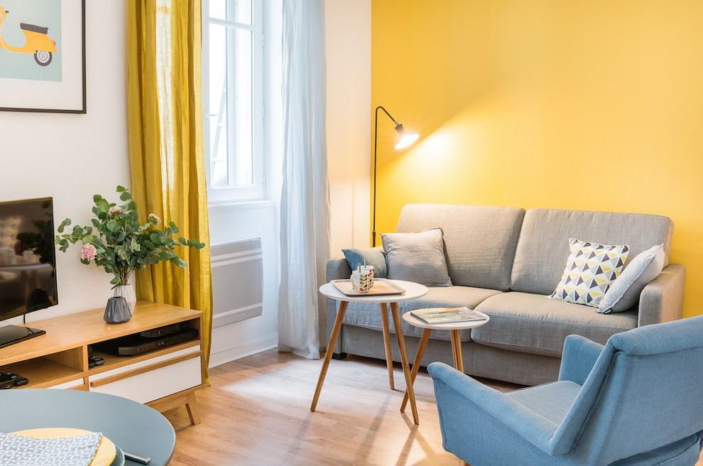 Серый диван на фоне желтой стены гостиной