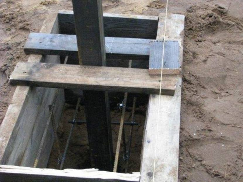 Опалубка из старых досок для заливки фундамента столба