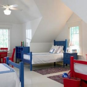 Красные и синие кровати в просторной комнате