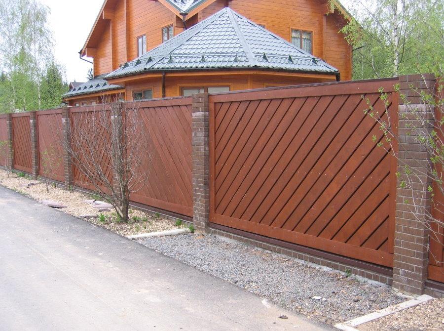 Деревянный забор на столбах из кирпича