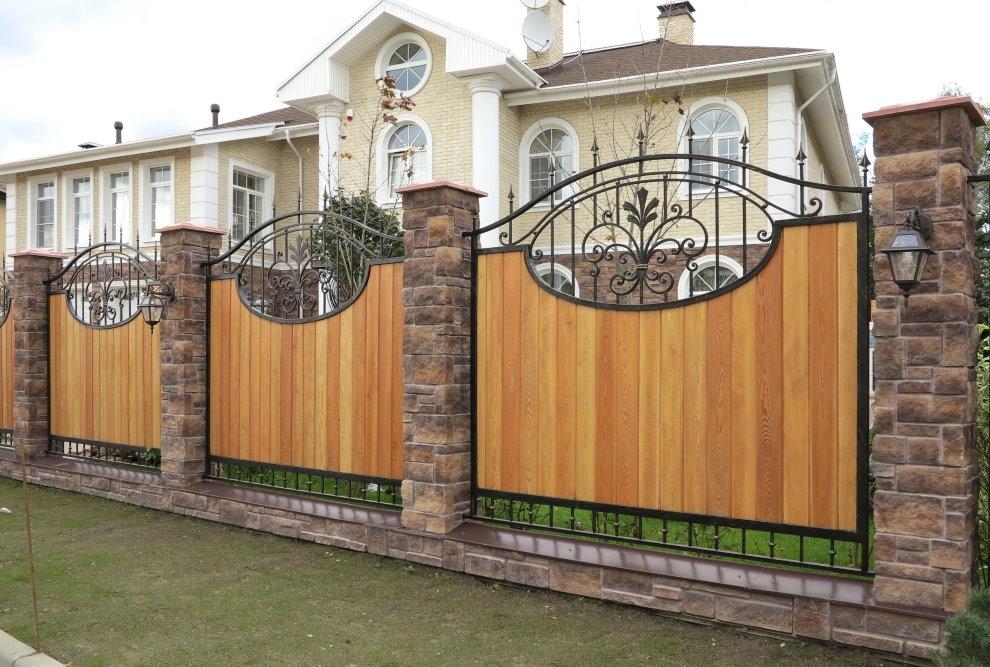 Деревянный забор с кованными элементами на каменных столбах
