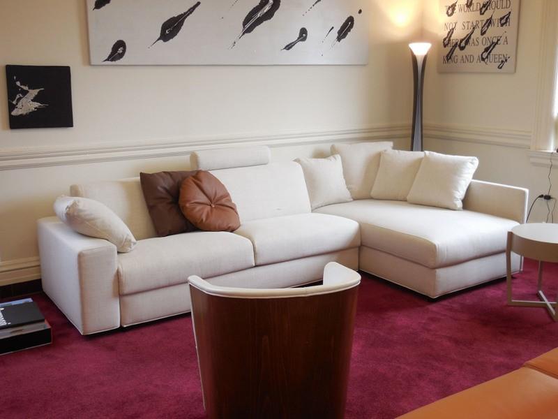 Бордовый ковер перед белым диваном