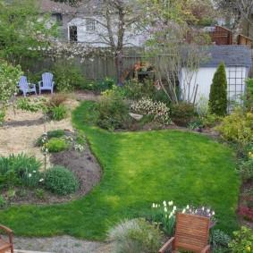 Сад на небольшом участке с деревянным забором