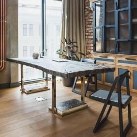 Стол в комнате стиля лофт с окном до пола