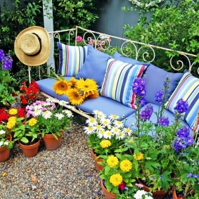 Садовая скамеечка в окружении цветущих растений