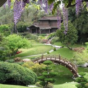 Деревянный мостик через пруд в саду