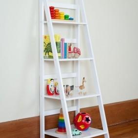 Белая полка-лесенка с детскими игрушками