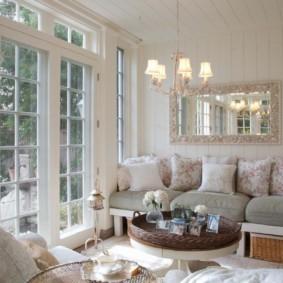 Зеркало в красивой рамке над диваном в частном доме