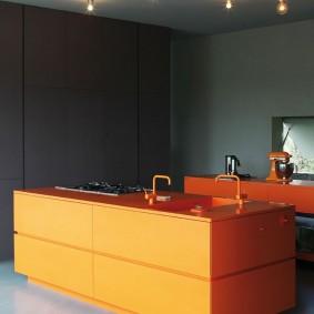 Оранжевый кухонный остров на фоне серых стен