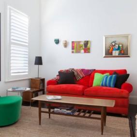 Красный диван около белой стены