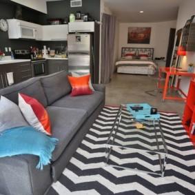 Серый диван напротив красной полки