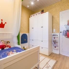 Белый шкаф в углу детской спальни