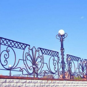 Садовые светильники на кованном заборе
