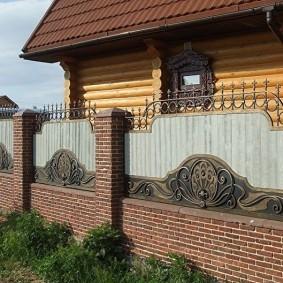 Кирпичный забор перед деревянным домом