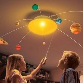 Люстра в виде солнечной системы на потолке детской