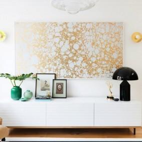 Панно из золотистых обоев на белой стене