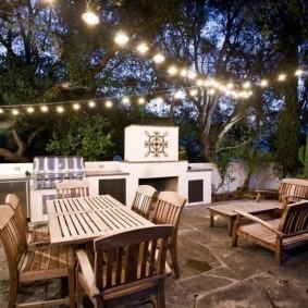 Гирлянды с лампочками над садовой мебелью