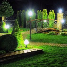 Мостик в саду с кипарисами и туями