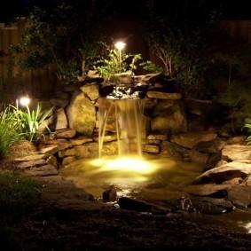 Садовые светильники на берегу водоема с водопадом