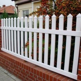 Забор с кирпичными столбами в палисаднике частного дома