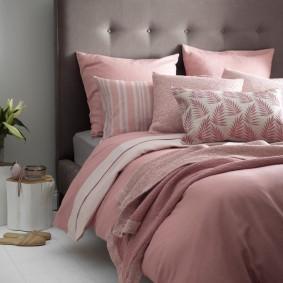 Розовые подушки на кровати с серым изголовьем
