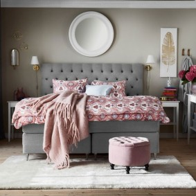 Серая кровать в спальне городской квартиры