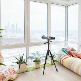 Домашний телескоп около панорамного окна
