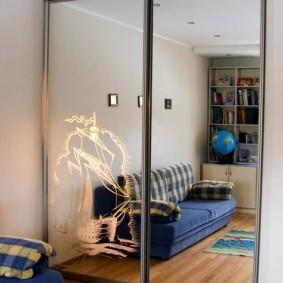 Отражение синего дивана в зеркальных дверцах шкафа