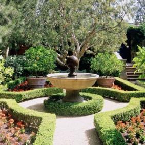 Стильный фонтан в саду регулярного ландшафта