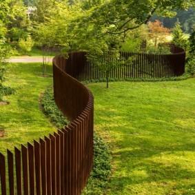 Извилистый забор из деревянных досок