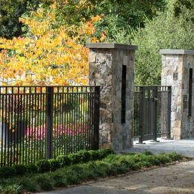 Каменные столбы на металлических воротах
