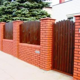 Деревянный забор на кирпичных столбах