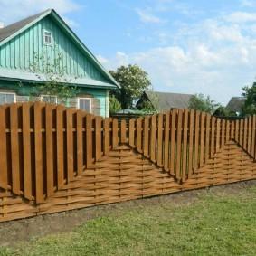 Красивый забор из дерева перед сельским домом