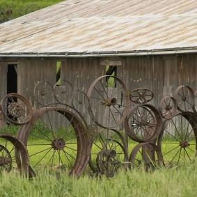 Изгородь на даче из старых металлических колес